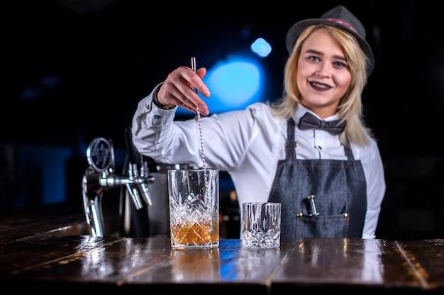 La camarera profesional da los toques finales a una bebida en el bar.
