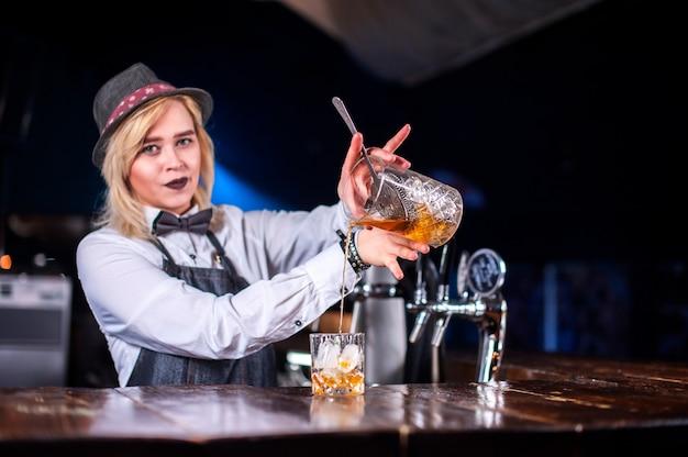 Camarera profesional formula un cóctel mientras está de pie cerca de la barra del bar
