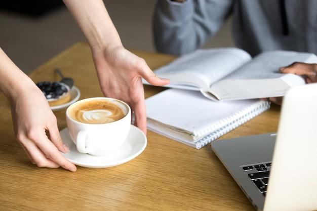 Camarera que sirve capuchino para el visitante de la cafetería en la mesa del café, primer plano
