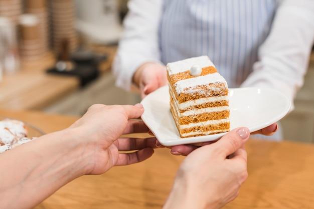 Una camarera que sirve pastelería en un plato blanco al cliente.