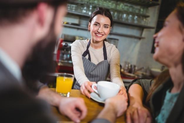 Camarera que sirve una taza de café a los clientes
