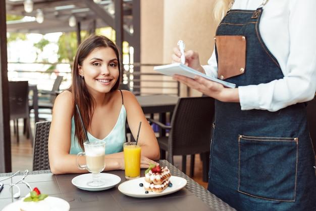 Camarera servidor ayudando a cliente en cafe