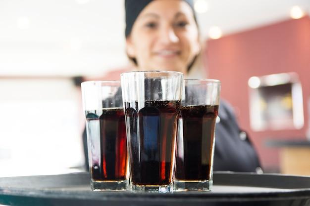 Camarera de sexo femenino que ofrece los vidrios de la bebida en la bandeja