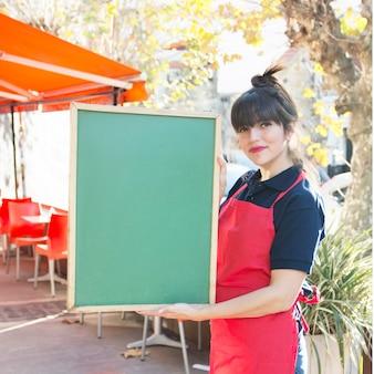 Camarera de sexo femenino que sostiene el tablero verde en blanco del menú en el café al aire libre