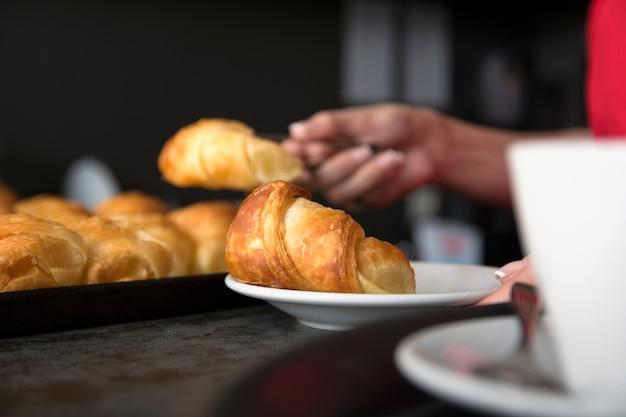 Camarera sirviendo croissant al horno en el plato blanco