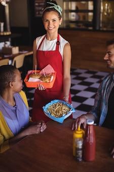 Camarera sirviendo hamburguesas y papas fritas al cliente