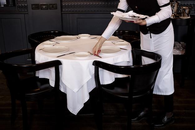 La camarera está sirviendo la mesa