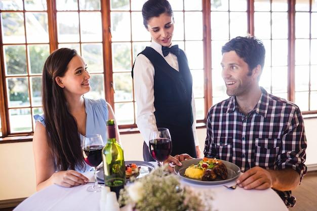 Camarera sirviendo plato de comida en la mesa de los clientes