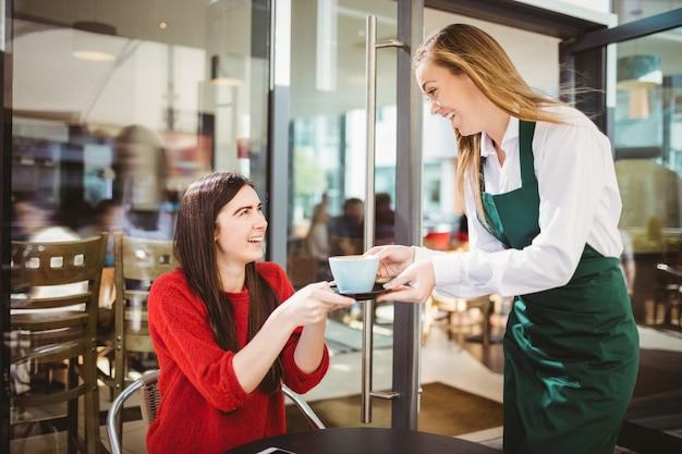 Camarera sirviendo una taza de café en la cafetería