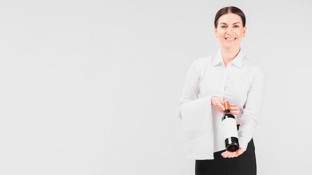 Camarera sonriendo y tapando botella de vino