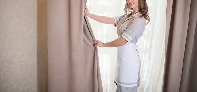 Camarera sonriente abriendo las cortinas de la habitación.