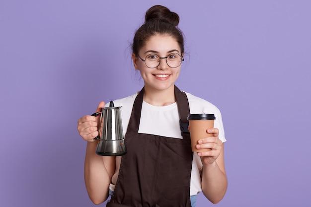 Camarera sonriente en camiseta blanca y delantal marrón con maceta y llevar la taza en las manos