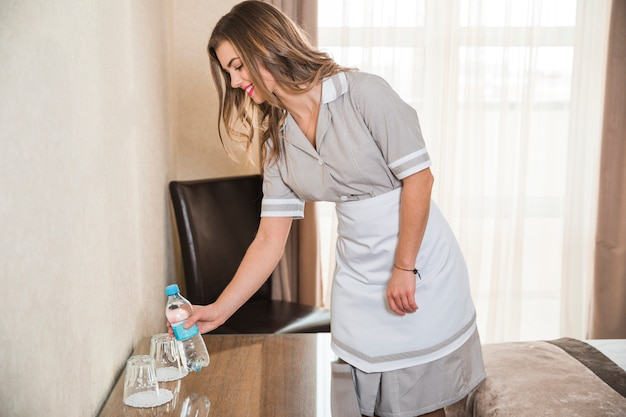 Camarera sonriente colocando la botella de agua sobre la mesa en la habitación del hotel