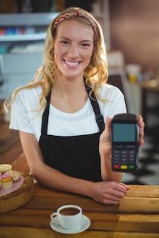 Camarera sonriente con lector de tarjetas de crédito