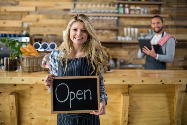 Camarera sonriente mostrando pizarra con señal abierta en café