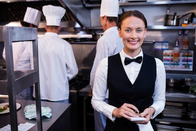 Camarera sonriente con notas en cocina comercial