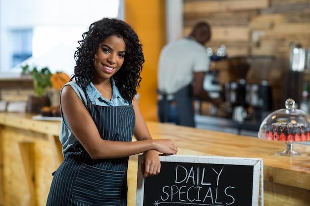Camarera sonriente de pie con menú junta en café