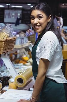 Camarera sonriente de pie en el mostrador de la cafetería