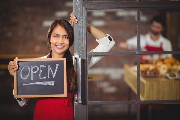 Camarera sonriente que muestra la pizarra con el signo abierto