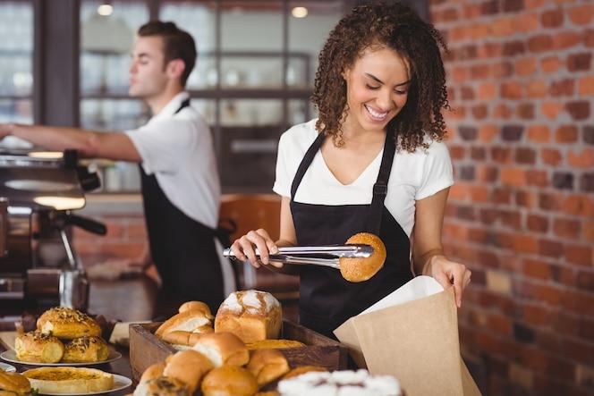 Camarera sonriente que pone el rollo de pan en bolsa de papel