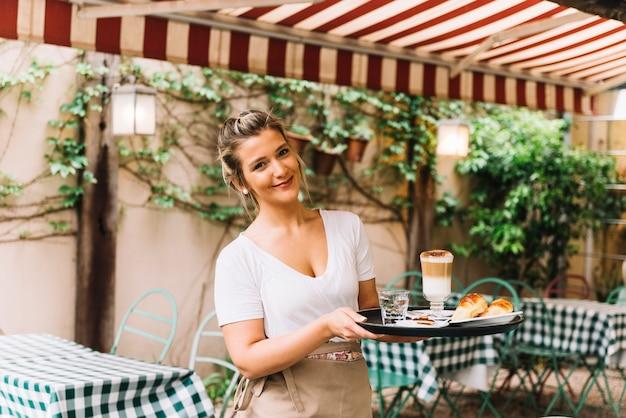 Camarera sonriente sosteniendo bandeja