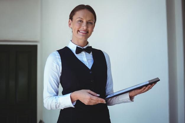 Camarera sonriente sosteniendo un menú