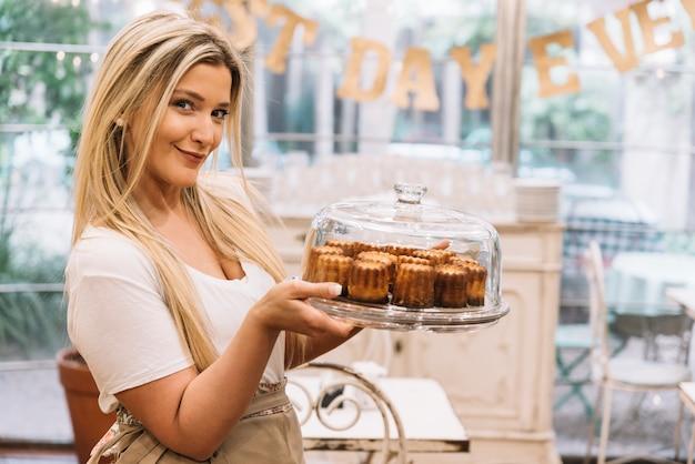 Camarera sosteniendo bandeja muffins