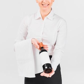 Camarera sosteniendo una botella de vino y sonriendo