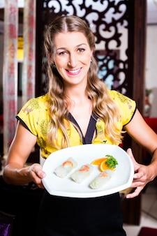 Camarera con sushi en restaurante asiático.