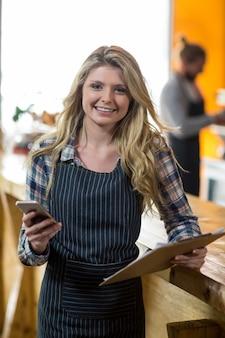 Camarera con teléfono móvil en el mostrador de café