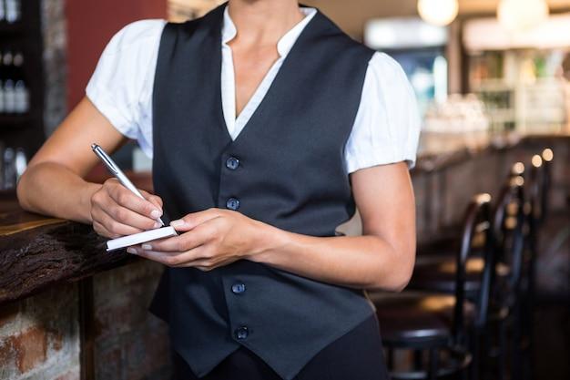 Camarera tomando orden en un cuaderno