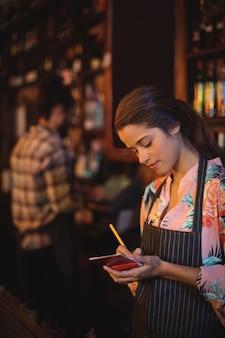 Camarera tomando un pedido en el bloc de notas en el mostrador