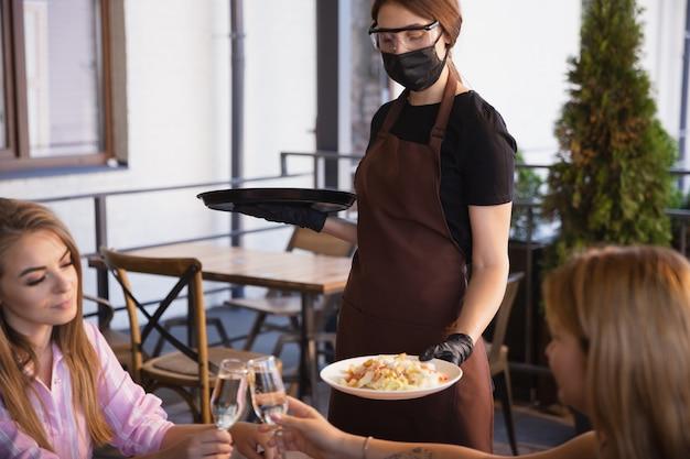 La camarera trabaja en un restaurante con una máscara médica, guantes durante la pandemia de coronavirus