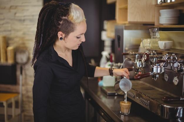 Camarera vertiendo leche en la taza de café en el mostrador