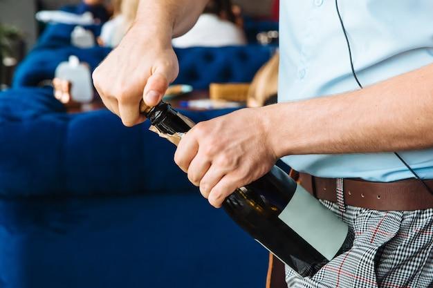 El camarero abre una botella de vino y saca el corcho.