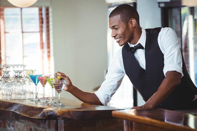 Camarero adornando cóctel con aceituna
