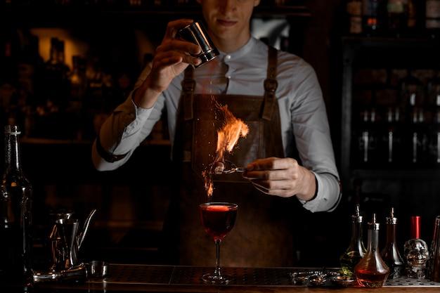 El camarero agrega especias para una decoración en el fuego sobre un delicioso cóctel rojo en el vaso