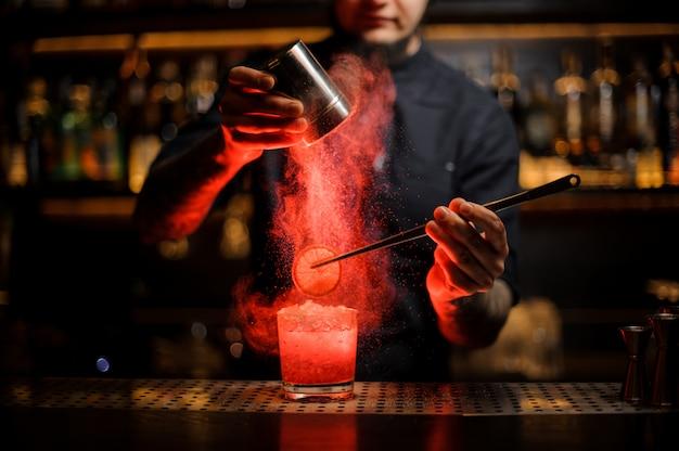 Camarero agregando especias en polvo en una copa de cóctel con una rodaja de limón
