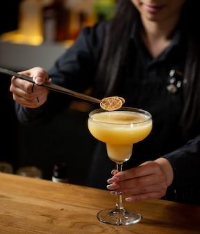 Camarero agregando rodajas de limón en cóctel de naranja.