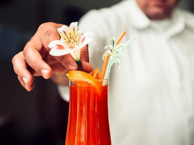 Camarero anónimo que sirve refrescante bebida en vaso