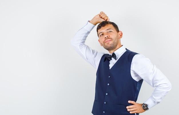 Camarero apoyando la cabeza en el puño levantado en camisa, chaleco y mirando soñador. vista frontal.