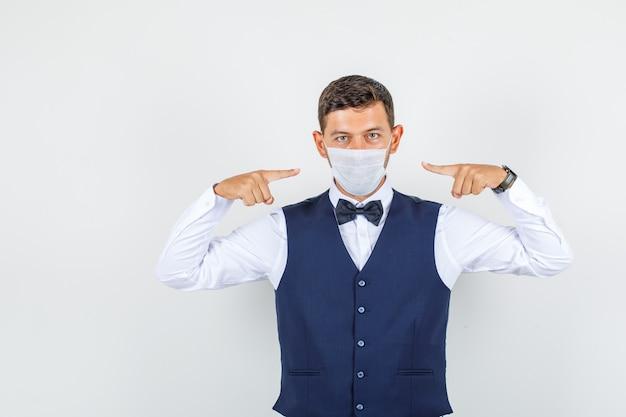 Camarero apuntando a la máscara médica en camisa, chaleco, vista frontal de la máscara.
