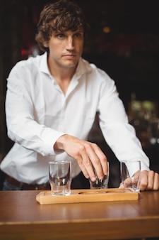Camarero arreglando el vaso de cerveza en la bandeja en la barra de bar