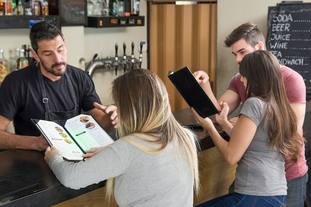 Camarero ayudando al cliente femenino mirando el menú en el mostrador de la barra