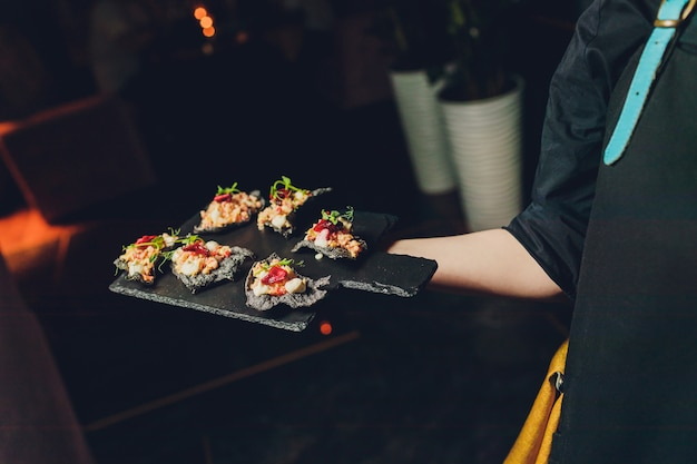 Un camarero con una bandeja de aperitivos en un banquete o recepción. catering buffet en la fiesta.