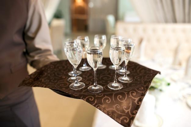 Camarero con bandeja recibe a los visitantes, vasos llenos de vodka.
