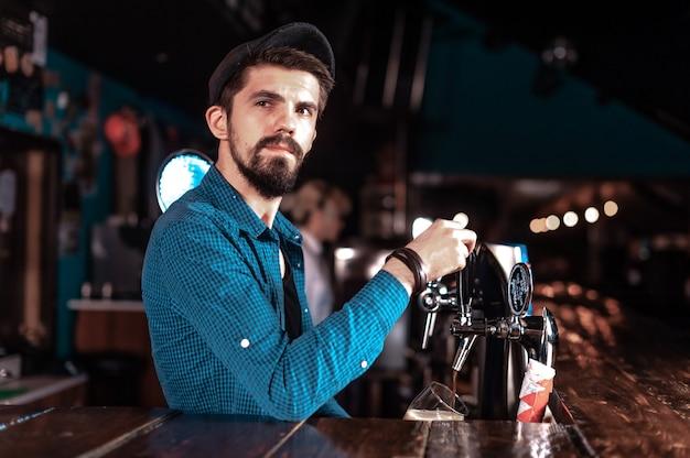Camarero barbudo vertiendo bebida alcohólica fresca en los vasos en el bar
