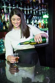 Camarero bastante vertiendo whisky en un vaso en barra de bar