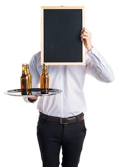 Camarero con botellas de cerveza en la bandeja con un cartel vacío