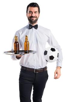 Camarero con botellas de cerveza en la bandeja de la celebración de un balón de fútbol